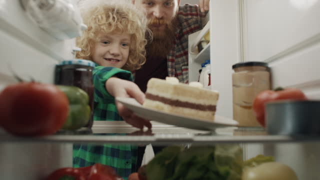 boy and father taking cake from refrigerator - open refrigerator stock videos & royalty-free footage
