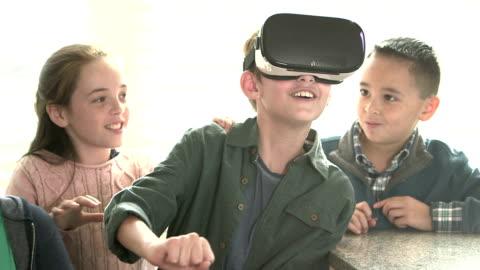 junge und freunde, spielen mit virtual-reality-kopfhörer - überbelichtet stock-videos und b-roll-filmmaterial
