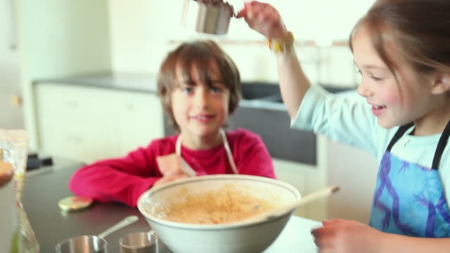 CU FOCUSING Boy (8-9) and girl (6-7) baking, girl pouring chocolate chips into cookie dough, Yarmouth, Maine, USA