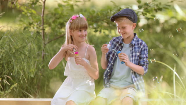 SLO MO Boy and girl blowing bubbles in nature