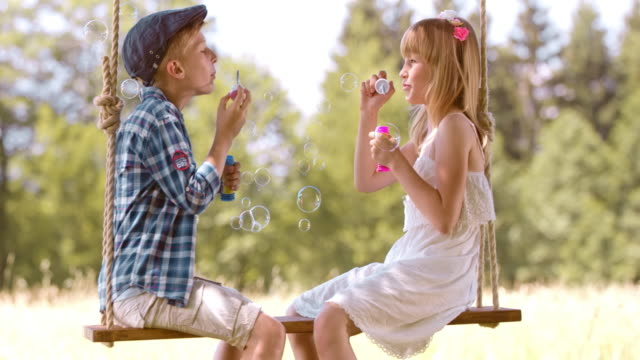 SLO MO Boy and girl blowing bubbles on a swing