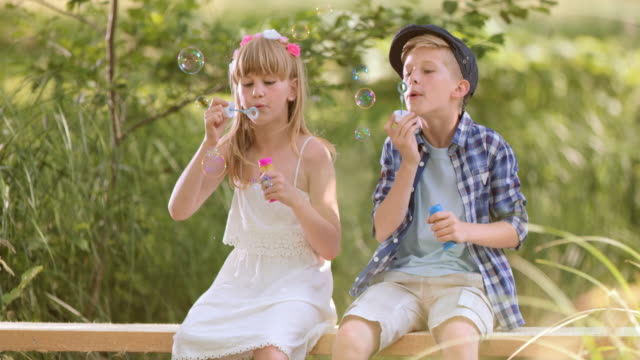 SLO MO – Jungen und Mädchen Blasen Blasen sitzen auf Fußgängerbrücke
