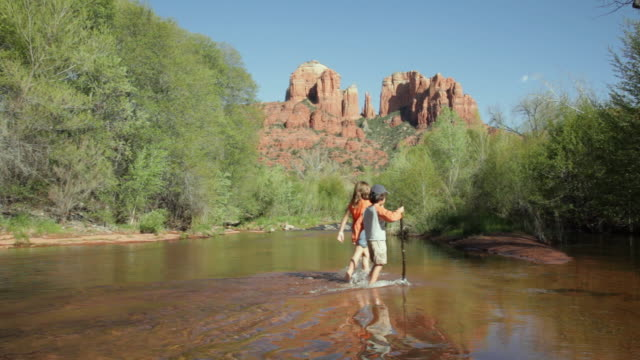 ws boy and girl (6-9) crossing oak creek, cathedral rock in background / sedona, arizona, usa - sedona stock videos & royalty-free footage