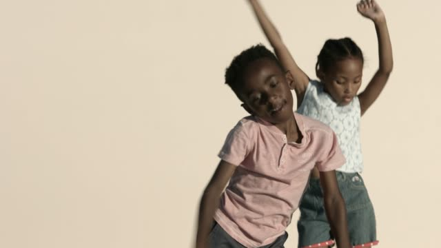 boy and girl dancing against beige background - children only stock videos & royalty-free footage