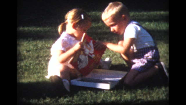 1959 boy and girl draw in coloring books, while family looks on
