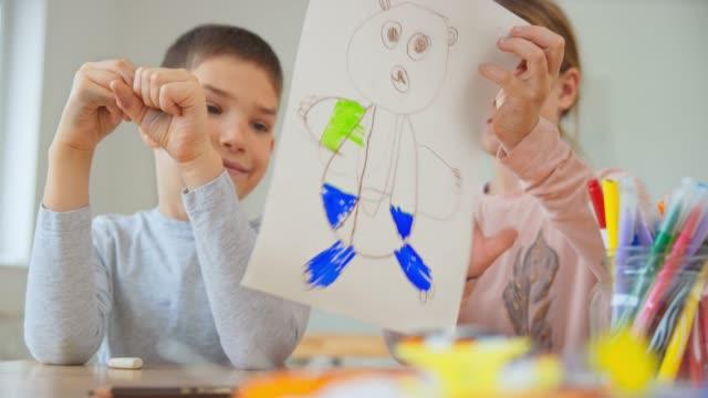 vidéos et rushes de garçon et fille dessinant un ours ensemble et montrant le dessin - young animal