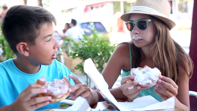 boy and girl eating donuts in a bakery - doughnut stock videos and b-roll footage