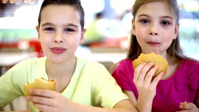 Jungen und Mädchen Essen fast food und enjoyoing.