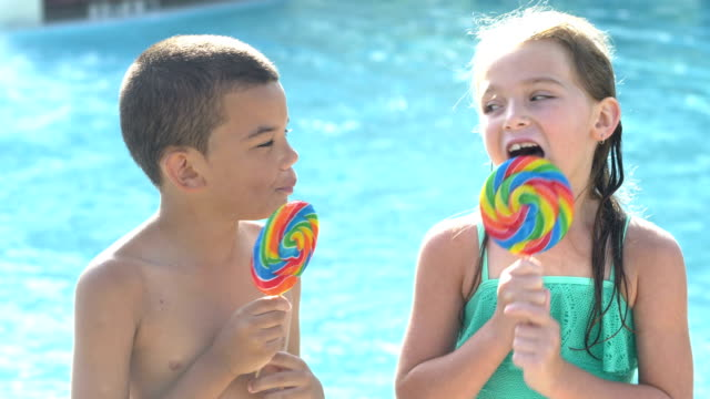 boy and girl enjoying lollipops at swimming pool - lollipop stock videos & royalty-free footage