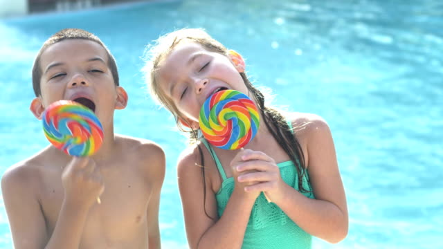 boy and girl enjoying lollipops at swimming pool - sticking out tongue stock videos & royalty-free footage