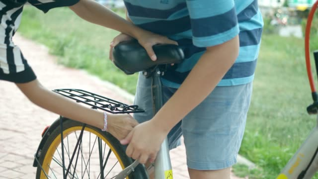 boy and girl fixing bicycle seat before ride, lifestyle cocnept. - bicycle seat stock videos & royalty-free footage