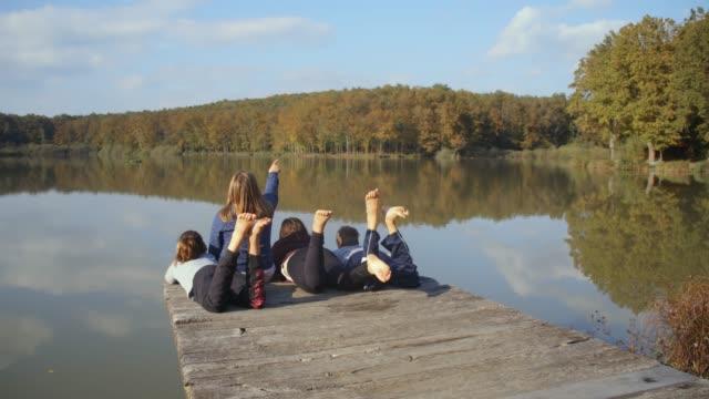 jungen und mädchen freunden entspannen, treten füße auf ruhigen see dock, real-time - kind vor der pubertät stock-videos und b-roll-filmmaterial
