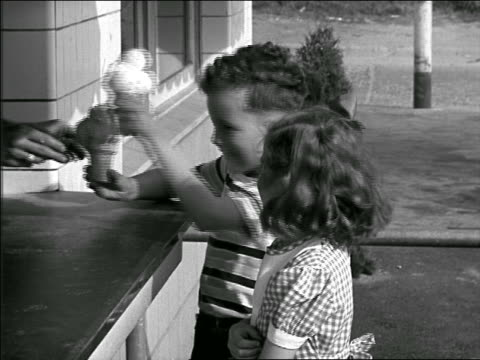 b/w 1949? boy and girl getting triple-scoop ice cream cones at counter outdoors - ice cream cone stock videos & royalty-free footage