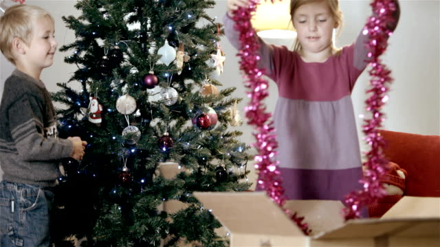 boy and girl hang decorations on tree - tinsel stock videos & royalty-free footage