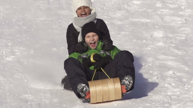boy and girl have fun sledding - winter sport stock videos & royalty-free footage