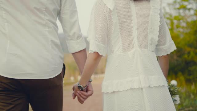 Menino e menina de mãos dadas perto do lago.