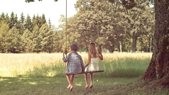 SLO MO Boy and girl holding hands sitting on swing