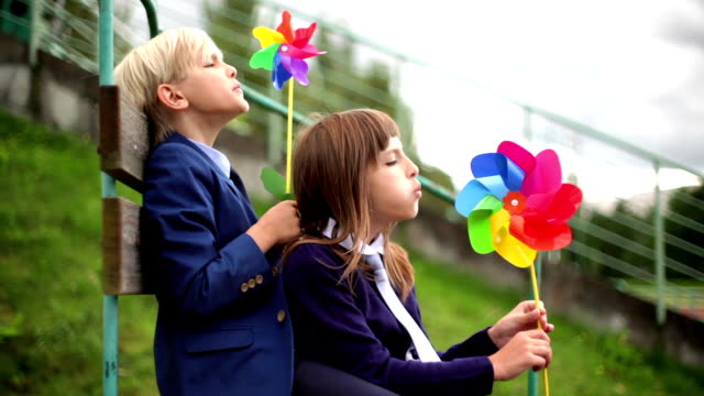 boy and girl holding up paper windmill at coast - girandola video stock e b–roll