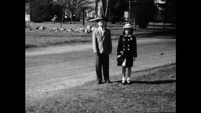 boy and girl in formal clothing posing and walking towards camera dog walks into frame houses and street in the background - formal stock videos & royalty-free footage