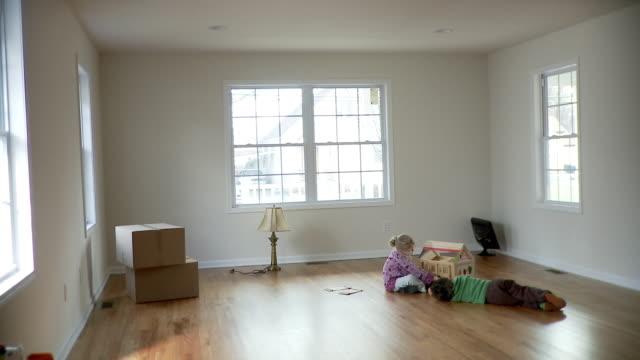 vídeos de stock, filmes e b-roll de ws, boy (2-3) and girl (4-5) in near-empty room with cardboard boxes, plainfield, new jersey, usa - caixa de papelão