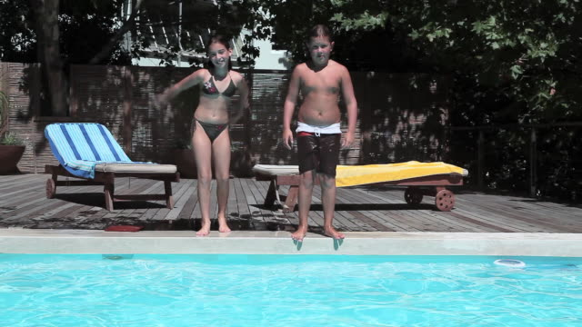 Boy and girl jumping into swimming pool