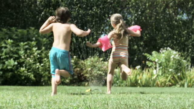 boy and girl jumping through water from garden sprinkler - schwimmflügel stock-videos und b-roll-filmmaterial