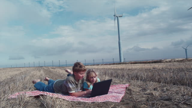 stockvideo's en b-roll-footage met ws boy and girl looking at laptop in field and wind turbines / zillah, washington, usa   - op de buik liggen