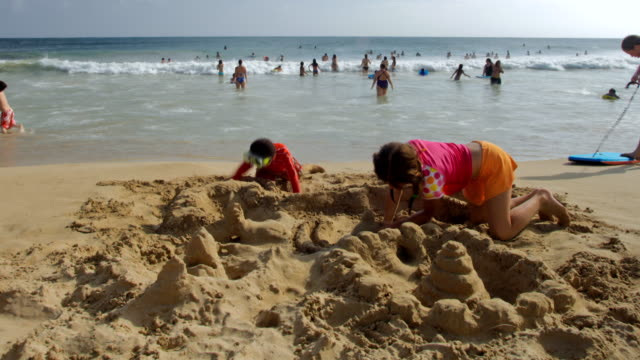 WS T/L Boy and girl making sand castle at beach with people in background / Poipu, Kauai, Hawaii, USA