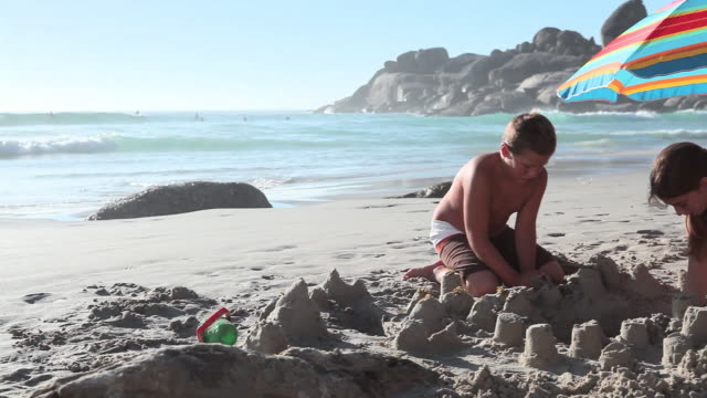 Boy and girl making sandcastles on beach