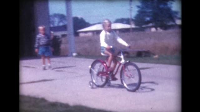vídeos de stock e filmes b-roll de 1960 boy and girl on bike with training wheels - bicicleta