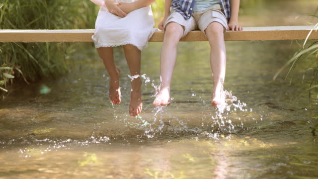 slo mo boy and girl on footbridge splashing water - sitting stock videos & royalty-free footage