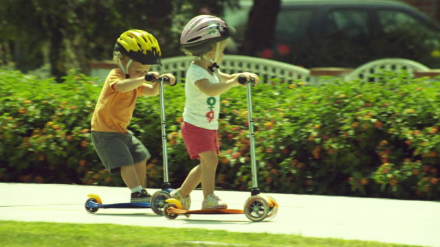 ms pan boy (2-3) and girl (4-5) on playing with push scooter / burbank, california, usa  - push scooter stock videos and b-roll footage