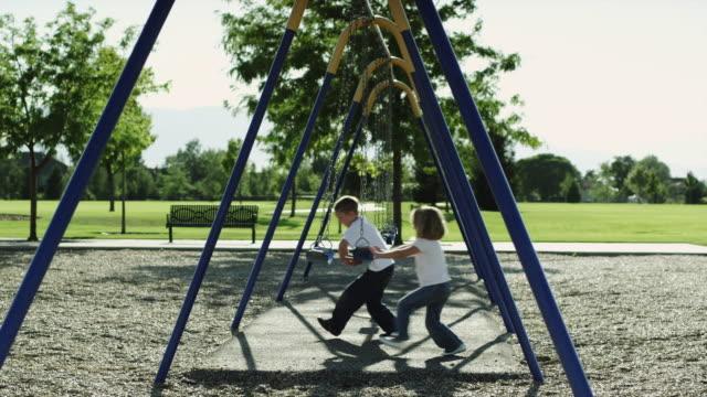 WS PAN SLO MO Boy (6-7) and girl (4-5) on swings in park / Orem, Utah, USA