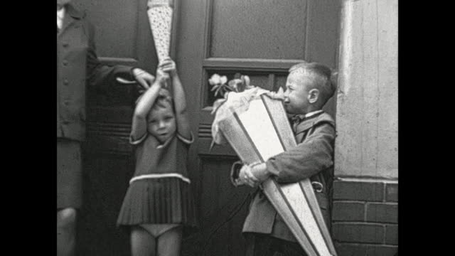 boy and girl on their first day of school, both presenting their cones full of treats to the camera, filmed with 9,5mm pathé / 1505009 - tag 1 stock-videos und b-roll-filmmaterial