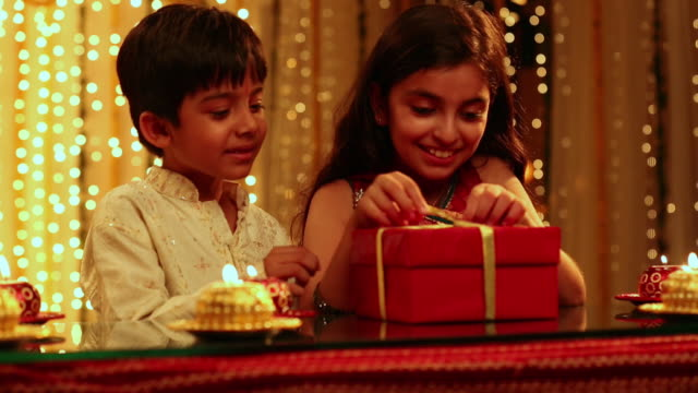 boy and girl opening a gift box in diwali festival - gift stock videos and b-roll footage