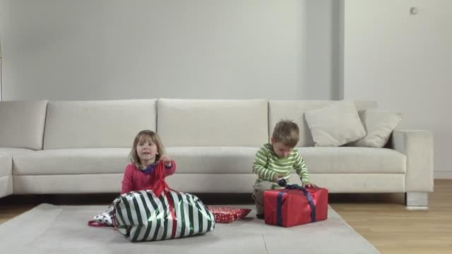 vídeos de stock, filmes e b-roll de ws boy (2-3) and girl (2-3) opening christmas presents / london, uk   - animal de brinquedo