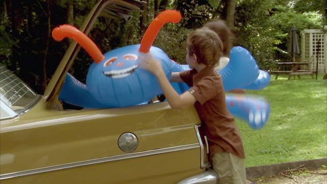 vídeos de stock, filmes e b-roll de ms, pan, boy (6-7) and girl (10-11) packing inflatable toy into car, tamborine mountain, brisbane, queensland, australia - leaving