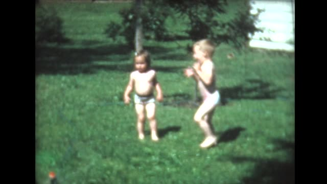 vidéos et rushes de 1961 boy and girl play in lawn sprinkler - brother