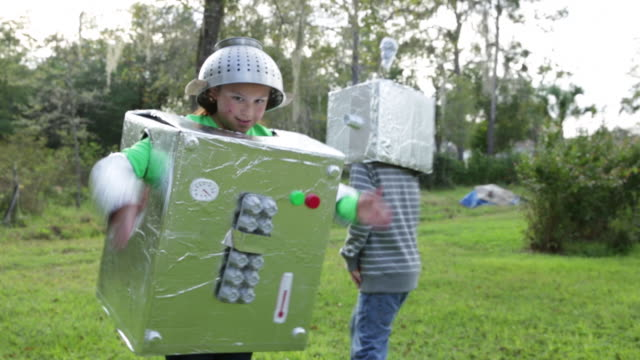 vídeos de stock e filmes b-roll de boy and girl play in robot costumes. - fantasia