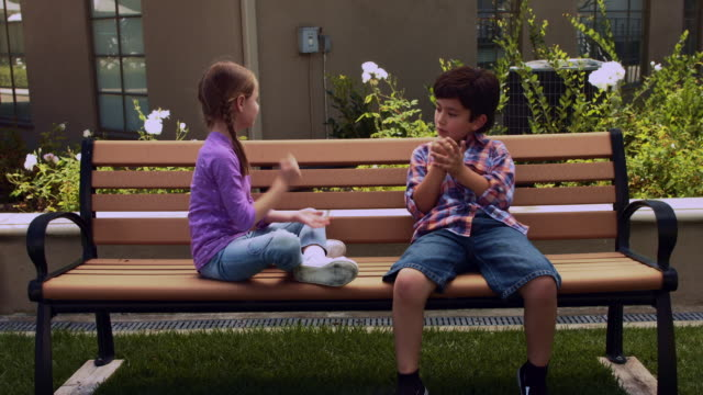 WS boy and girl play on a bench