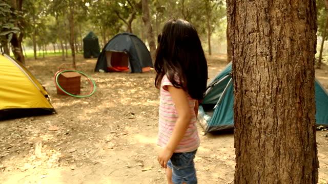 vídeos de stock, filmes e b-roll de boy and girl playing hide and seek game in the park, delhi, india - esconder