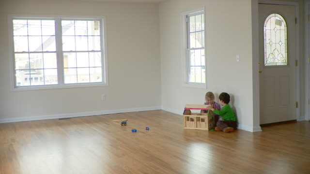 ws, boy (2-3) and girl (4-5) playing in empty room, plainfield, new jersey, usa - model house stock videos and b-roll footage