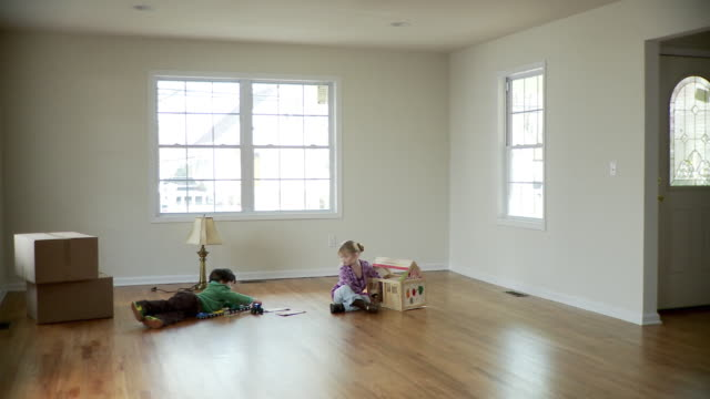 WS, PAN, Boy (2-3) and girl (4-5) playing in near-empty room with cardboard boxes, Plainfield, New Jersey, USA