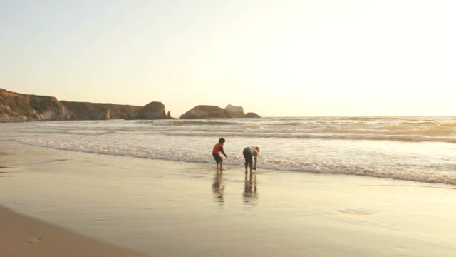 WS Boy (4-5) and girl (6-7) playing on beach at sunset, Big Sur, California, USA