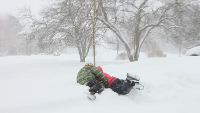 WS PAN ZI Boy and girl playing rugby during snowstorm / Yarmouth, Maine, USA