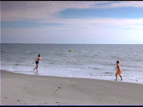 boy and girl playing with flying disk on beach - see other clips from this shoot 1335 stock videos and b-roll footage