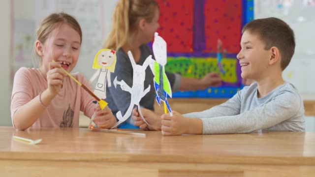 boy and girl playing with paper puppets in the classroom - elementary age stock videos & royalty-free footage