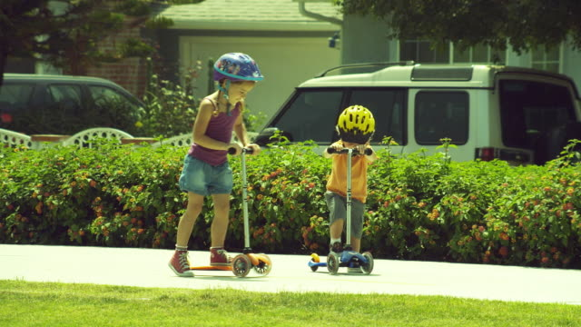 ms pan boy (2-3) and girl (4-5) playing with push scooter / burbank, california, usa  - push scooter stock videos and b-roll footage