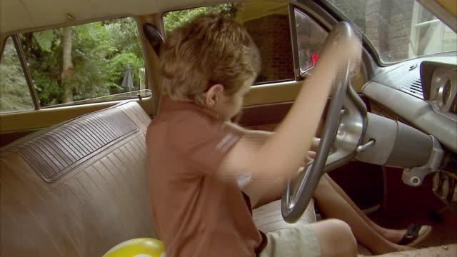 ms, boy (6-7) and girl (10-11) pretending to drive car, tamborine mountain, brisbane, queensland, australia - vintage car stock videos and b-roll footage