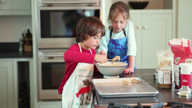 ms boy (8-9) and girl (6-7) putting cookie batter on baking sheet, yarmouth, maine, usa - baking sheet stock videos & royalty-free footage